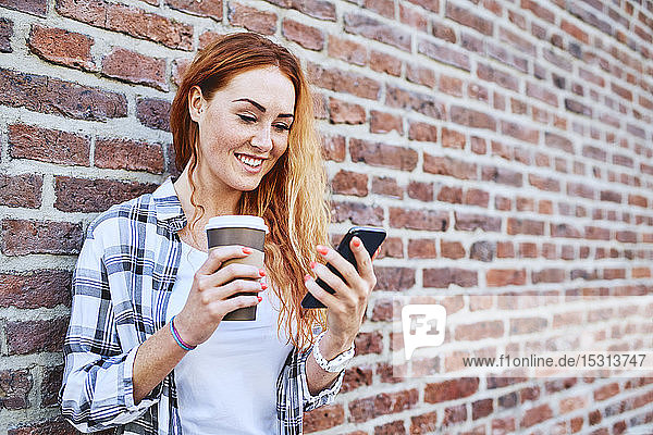 Young woman standing against brick wall using smartphone and holding coffee cup