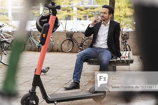 Geschäftsmann mit Kaffee zum Mitnehmen und E-Scooter in der Stadt