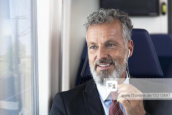 Älterer Geschäftsmann im Zug sitzend  mit Kopfhörern