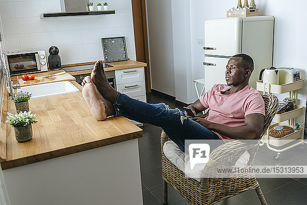 Young man with cell phone sitting relaxed in the kitchen at home