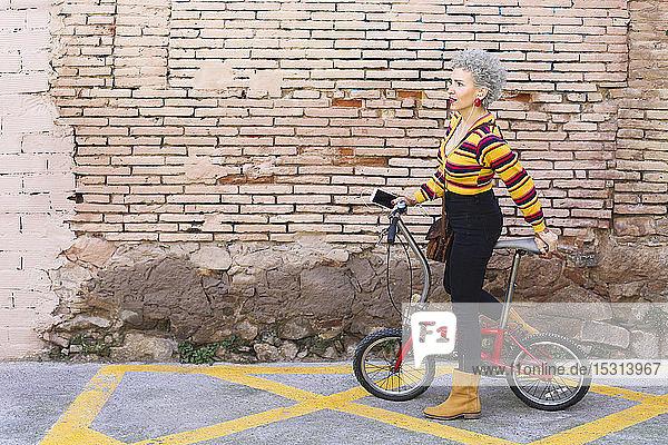 Modische reife Frau mit Fahrrad und Smartphone auf der Straße