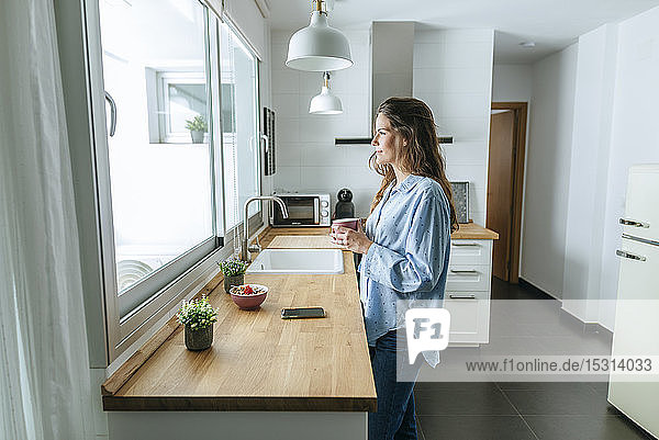 Young woman wearing pyjama in kitchen at home looking out of window