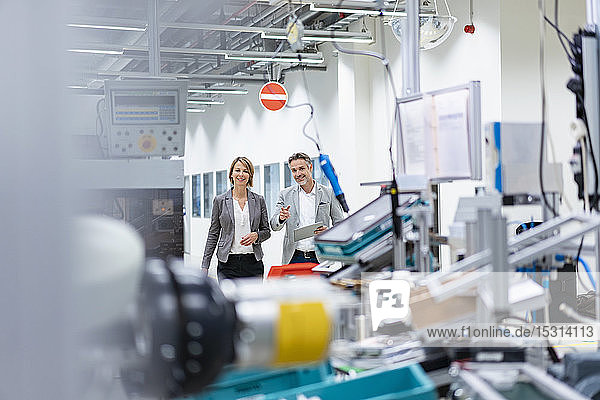 Smiling businesswoman and businessman with tablet talking in a modern factory