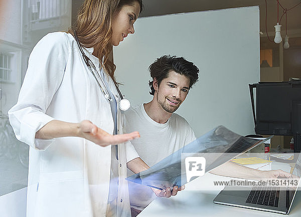 Two doctors discussing x-ray image at desk