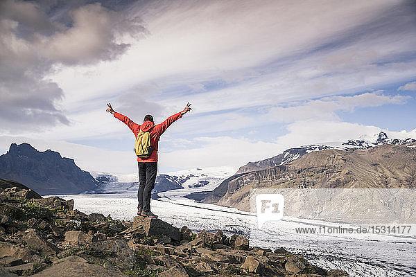 Ein erwachsener Mann steht im Skaftafell-Nationalpark und schaut auf den Vatnajokull-Gletscher  Island