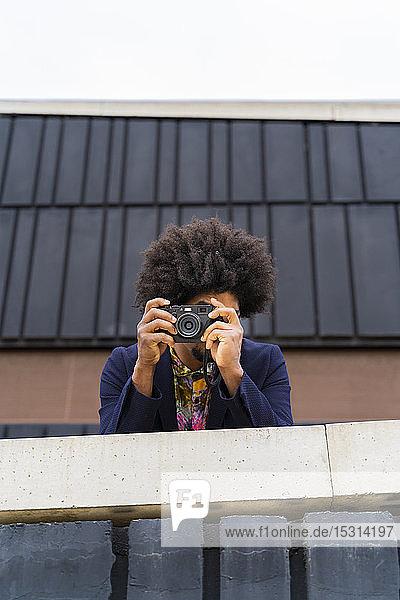 Stilvoller Mann beim Fotografieren mit einer Kamera