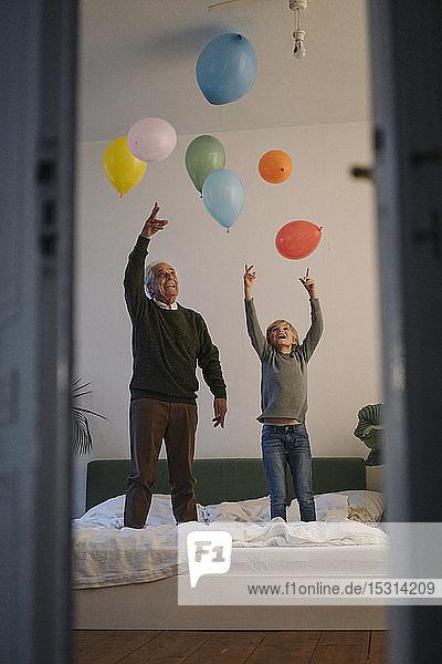 Glücklicher Grossvater und Enkel spielen zu Hause mit Luftballons auf dem Bett