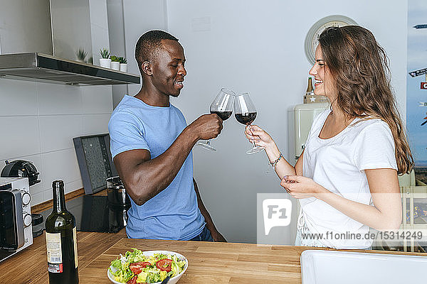 Couple toasting with wine in the kitchen