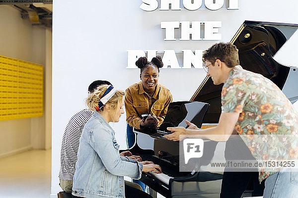 Schülerinnen und Schüler amüsieren sich beim gemeinsamen Klavierspielen