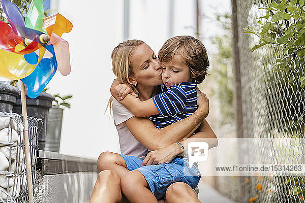 Mother snd son hugging and kissing in garden