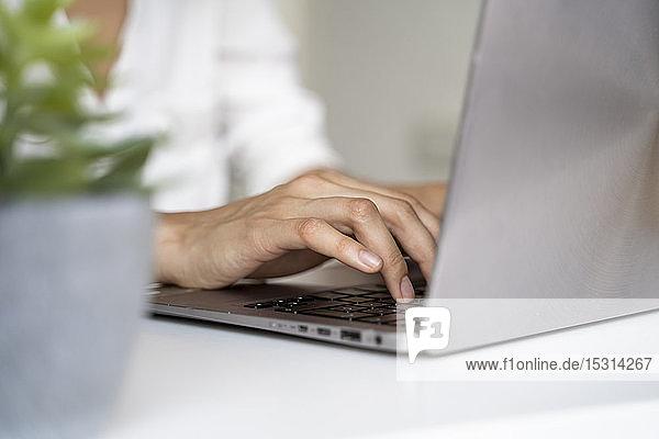 Nahaufnahme einer Frau mit Laptop am Schreibtisch