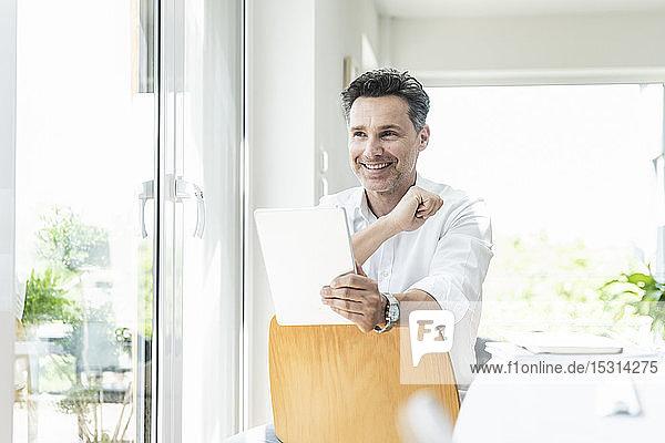 Mature man sitting on chair backwards  using digital tablet