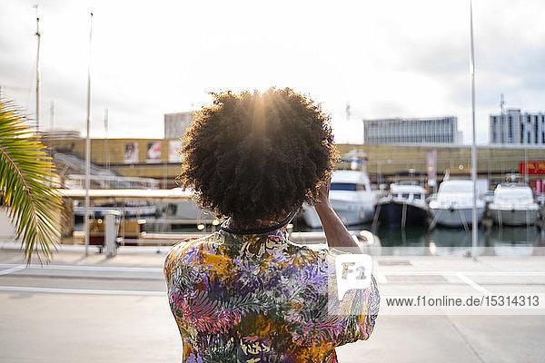 Rückansicht eines Mannes mit einer Kamera  der ein buntes Hemd trägt