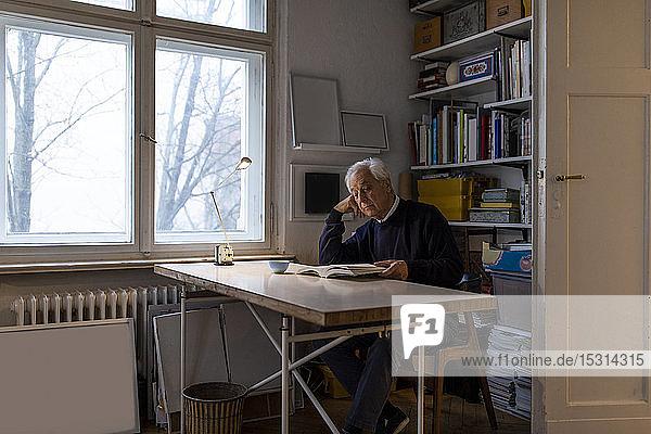 Senior man reading book at home
