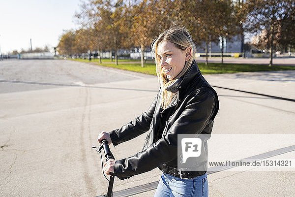 Smiling young woman with kick sccoter
