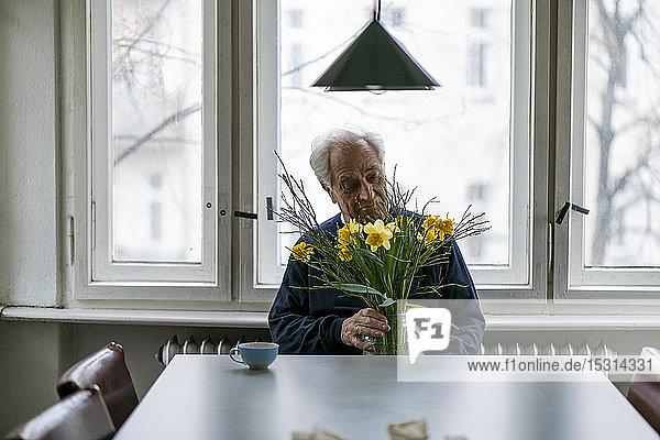 Älterer Mann mit Blumenstrauss zu Hause