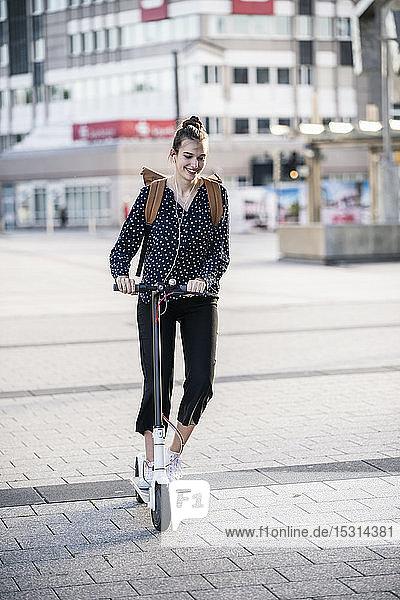 Junge Frau fährt Elektroroller in der Stadt