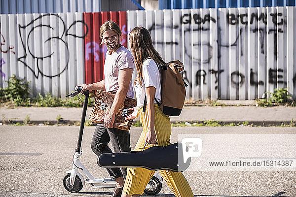 Junges Paar mit Elektroroller auf der Straße