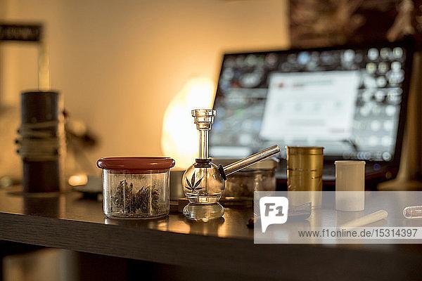 Marihuana im Glas  mit Haschpfeife und Joint auf dem Tisch
