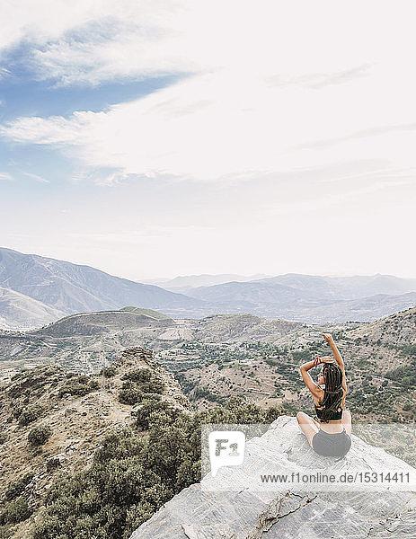 Rückansicht einer sportlichen jungen Frau  die auf einem felsigen Aussichtspunkt sitzt