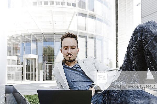 Porträt eines jungen Geschäftsmannes  der seinen Laptop im Freien benutzt