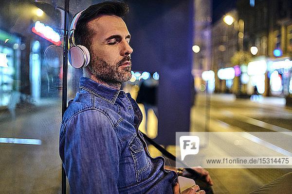 Mann mit schnurlosen Kopfhörern döst beim Warten auf den Nachtbus in der Stadt