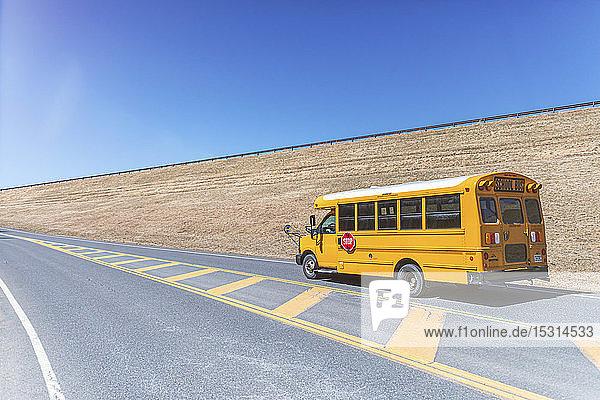 Gelber Schulbus auf der Autobahn vor strahlend blauem Himmel