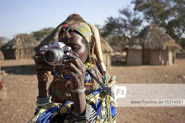 Traditionelle Muhila-Frau  die mit einer Kamera fotografiert  Kehamba  Chibia  Angola