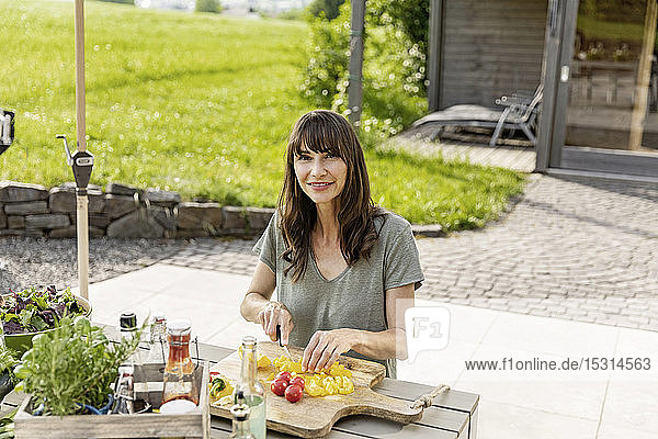 Portrait of smiling woman preparing a salad on garden table