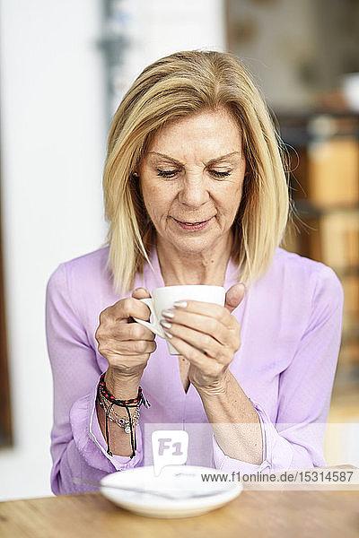 Reife Frau  die Kaffee trinkt und an einem Tisch im Freien in einem Café sitzt