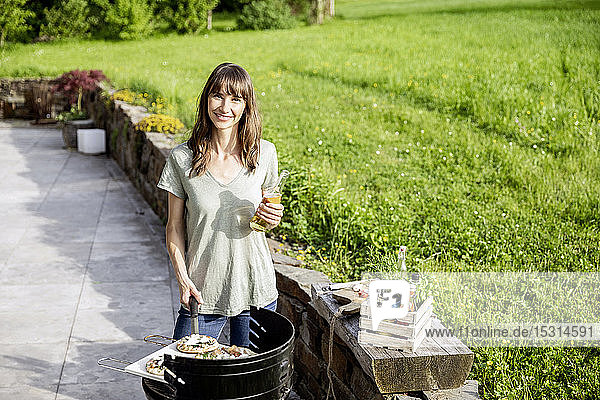 Portrait of smiling woman preparing food on barbecue grill