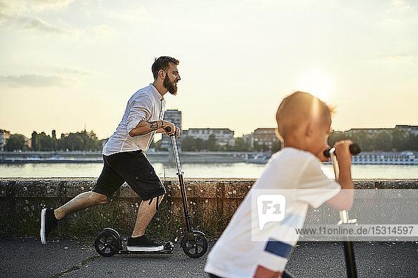 Vater und Sohn fahren Roller am Flussufer