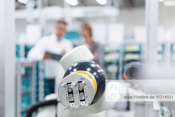 Assembly robot in a factory with business people in background