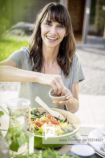 Porträt einer lächelnden Frau  die einen Salat auf dem Gartentisch zubereitet