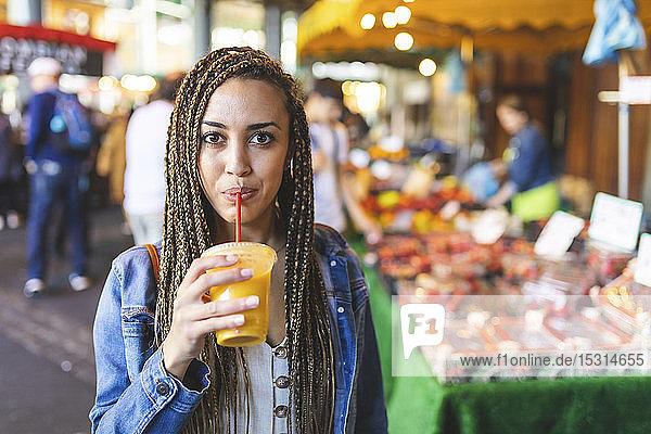 Porträt einer jungen Frau  die auf einem Straßenmarkt frischen Orangensaft trinkt  London  UK