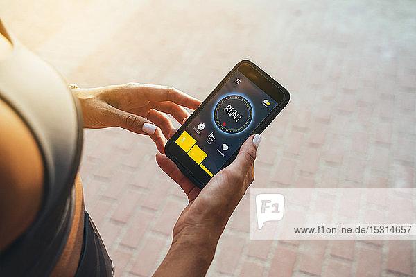 Sportler  der eine laufende App auf einem Smartphone verwendet