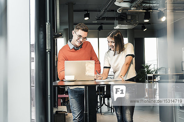Casual businessman and woman with laptop meeting in office