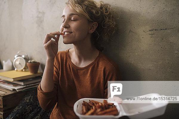 Porträt einer jungen Frau  die zu Hause Pommes Frites isst