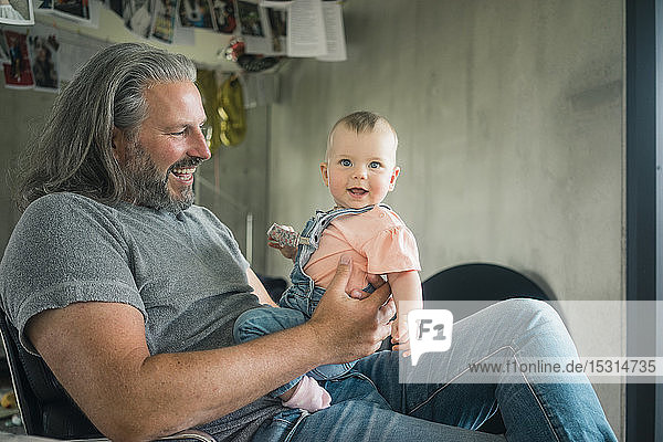 Happy mature man holding baby girl at home