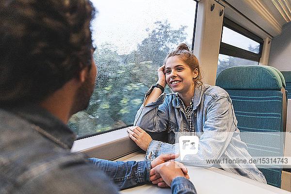 Porträt einer lächelnden jungen Frau  die mit ihrem Freund im Zug reist  London  UK