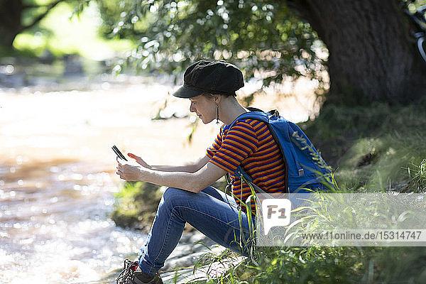 Frau mit Rucksack sitzt am Flussufer und schaut auf ihr Smartphone