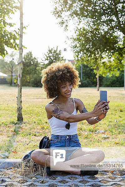 Porträt einer tätowierten jungen Frau  die sich im Sommer mit einem Smartphone selbstständig macht