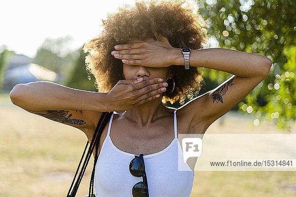 Tätowierte junge Frau  die Mund und Augen mit ihren Händen bedeckt