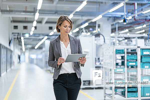 Businesswoman with tablet in a modern factory