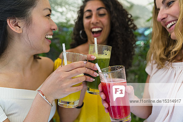 Three happy young women toasting with healthy drinks