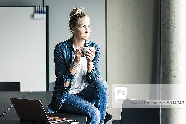 Smiling businesswoman sitting on table in office having a coffee break