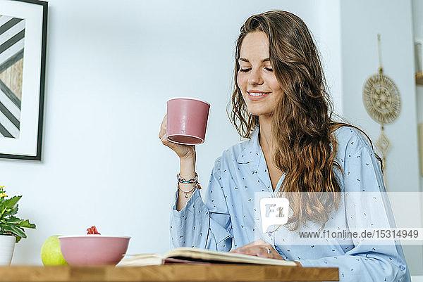 Lächelnde junge Frau liest während des Frühstücks zu Hause