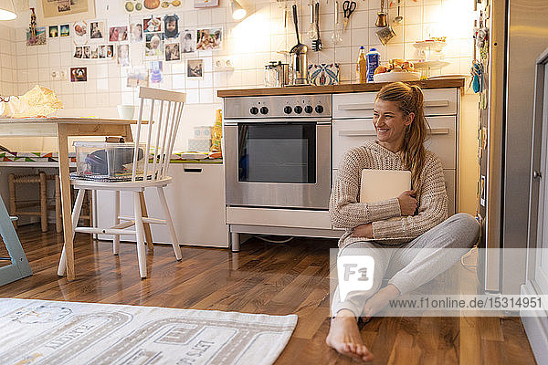 Young woman sitting on the floor in kitchen at home holding laptop