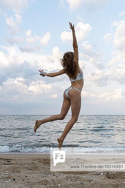 Junge Frau springt vor Freude am Strand
