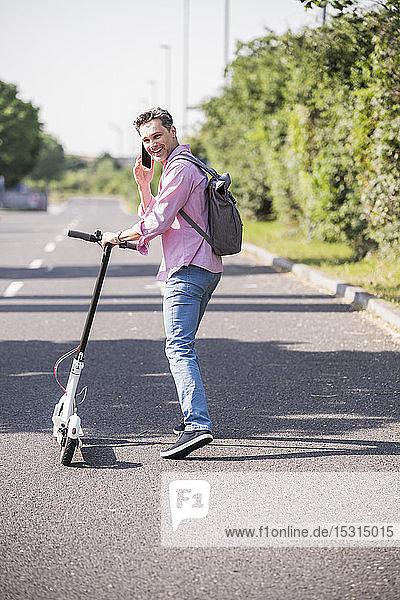 Geschäftsmann benutzt Smartphone  schiebt seinen E-Scooter